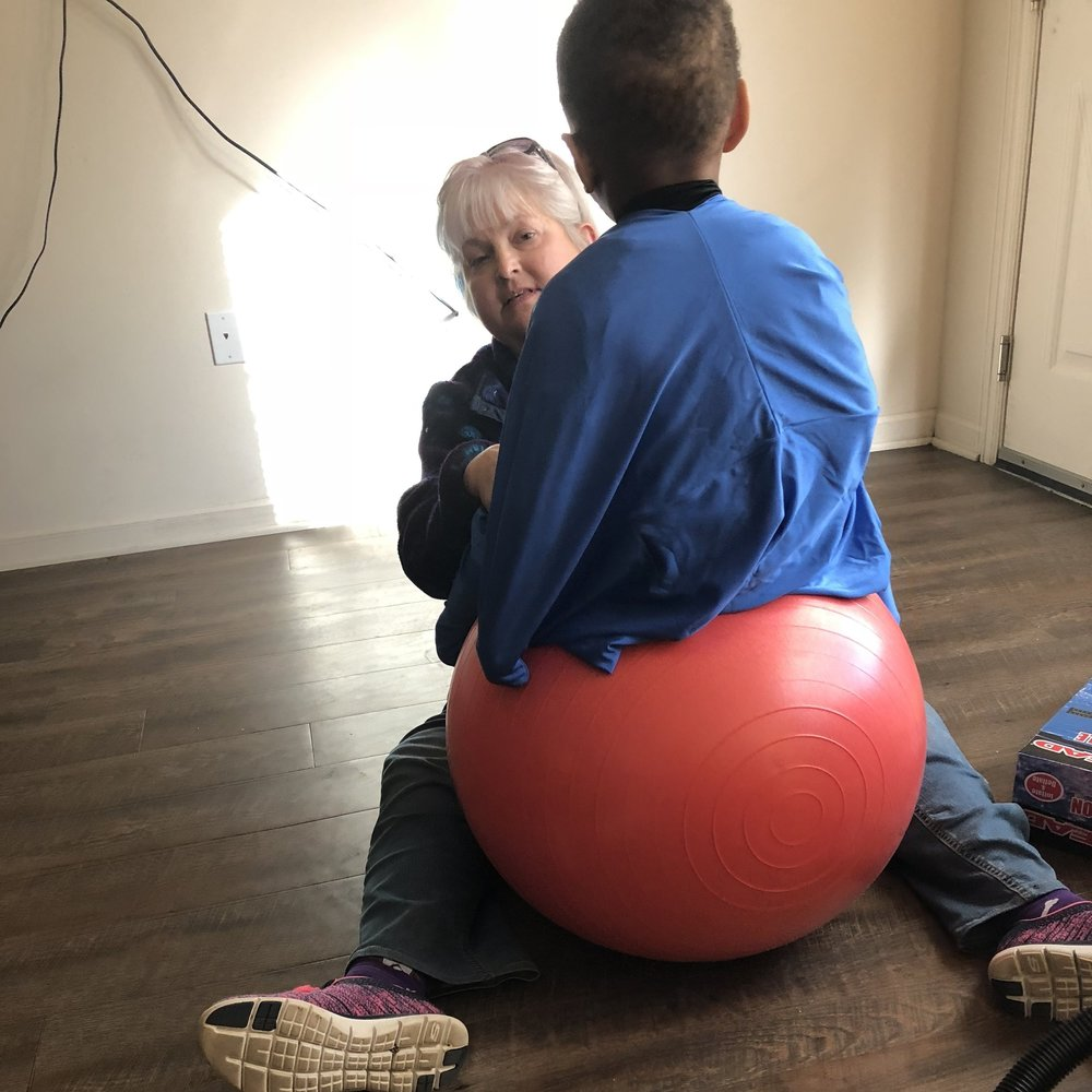 SIre's PT works on his focus while wearing the sensory sack on the yoga ball.