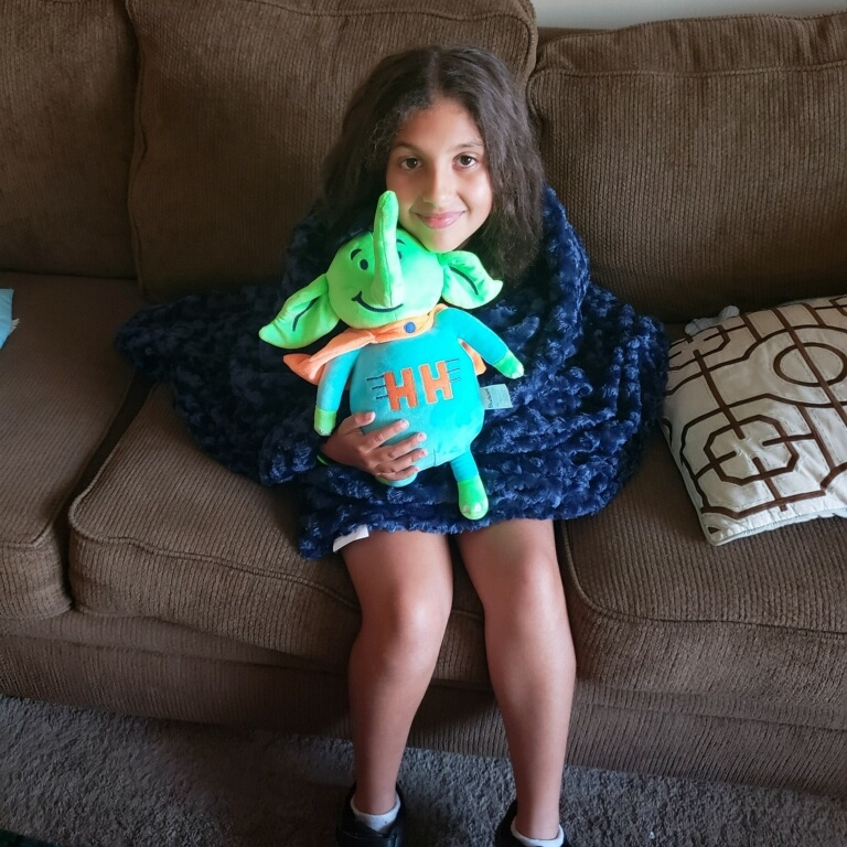 Giada snuggling up on her couch with Holton the Elephant and her new weighted blanket.