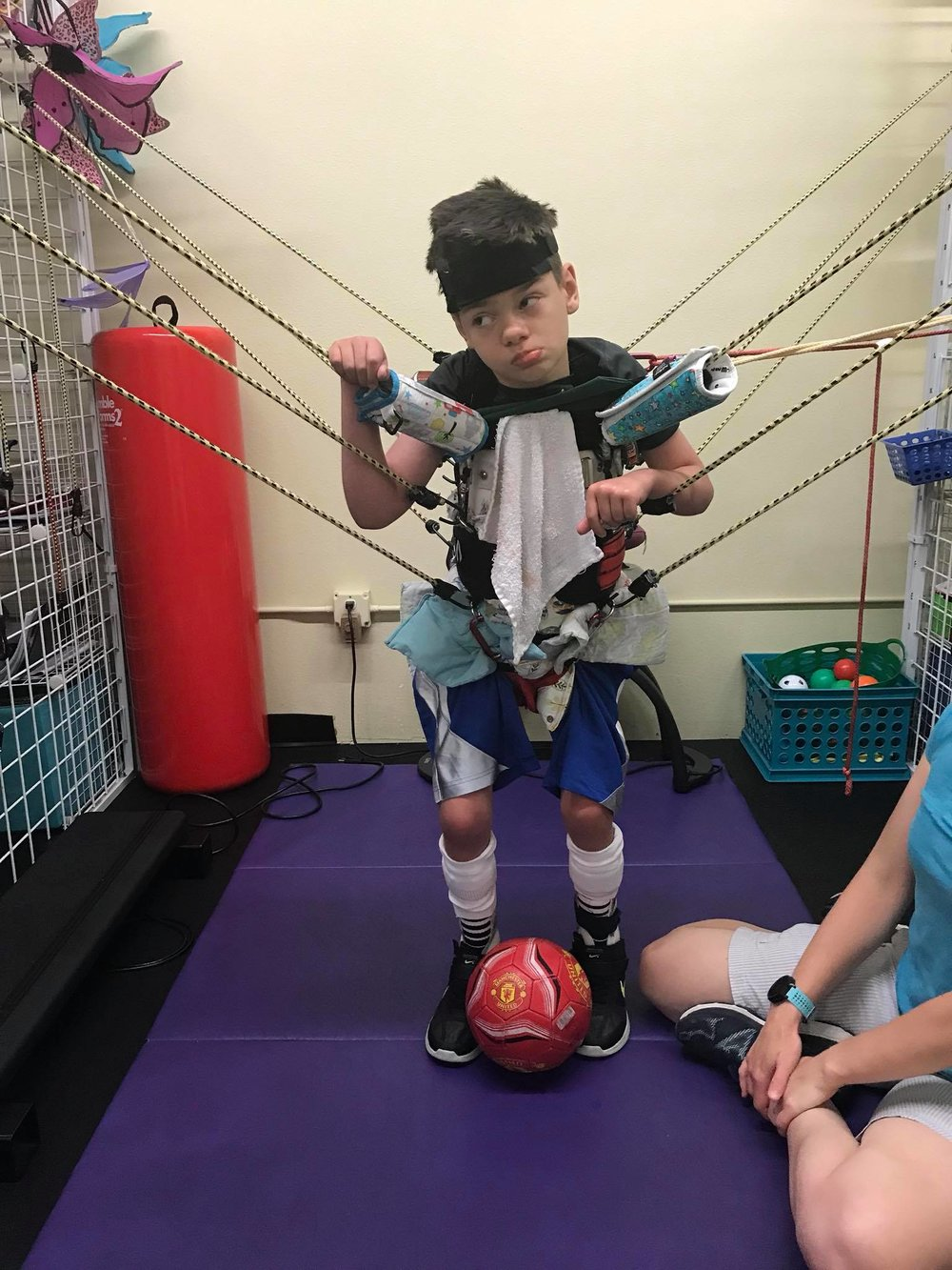 "Gabriel working hard in a ""SpiderCage"" which allows him to perform balance and strengthening exercises."