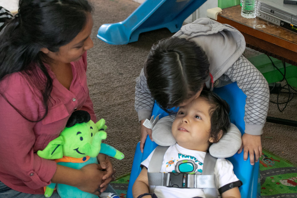 Matthew's mother Ana looks on as her son Max gives his little brother a kiss on the forehead while seated in the new Tumbleforms chair.
