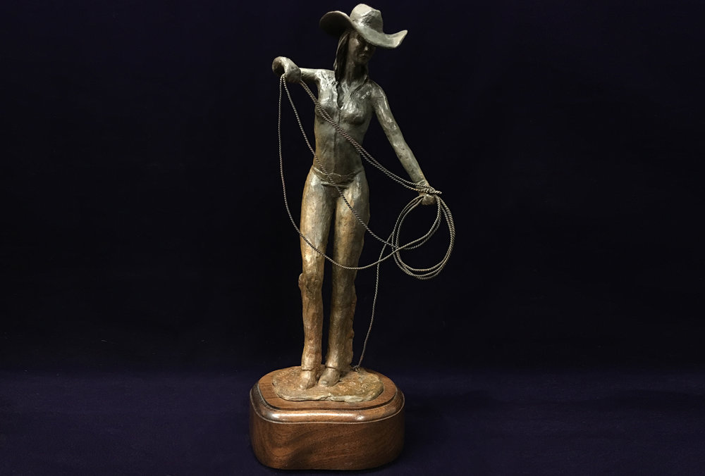 Cowgirl | 2016  A bronze sculpture of a cowgirl shaping her rope.
