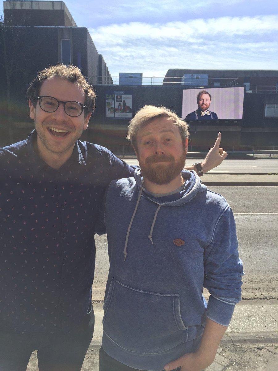 Olly and Ollie bear witness to a mid-sized billboard of Ollie's face. In Slough.