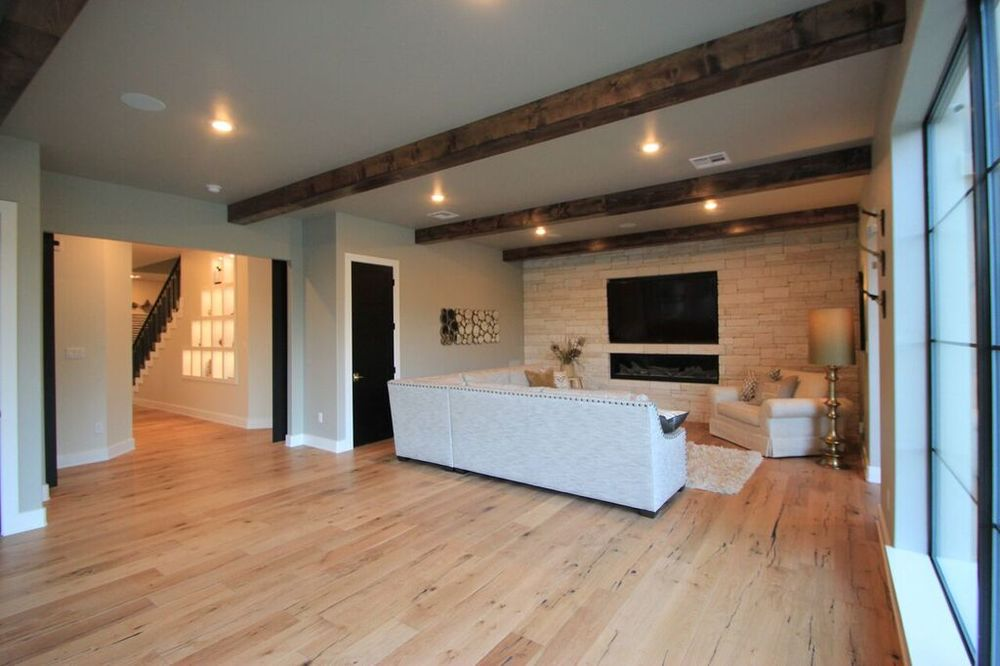 Modern elements in this space such as the fireplace, modern style sofa and black doors balance nicely with the rustic elements displayed in the rock wall and warm wood beams.
