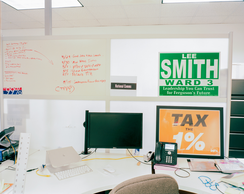 A desk at the Working Family Party of New York office is depicted with various party slogans.