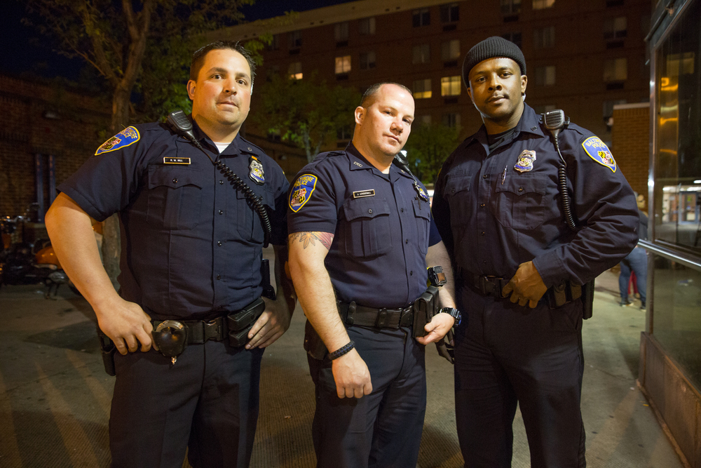 Three members of the Baltimore Police department stand guard near the West Baltimore CVS which had been looted and set ablaze earlier in the week just ahead of the 10PM curfew.