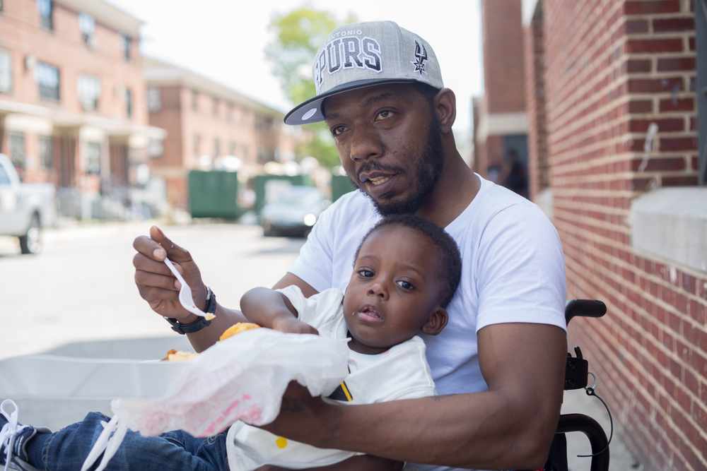 Marvin Jackson 39 feeds his son, Juwan Jackson, 2, in the Sandtown housing project where Freddie Gray resided.