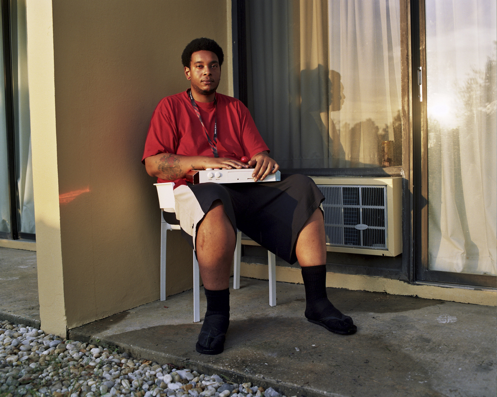Daniel Williams, 24, sits outside his hotel room in the early morning with his arcade stick at the CEO gaming tournament, in Orlando, Florida. He drove over 12 hours from Memphis, Tenessee with some friends to attend and compete.