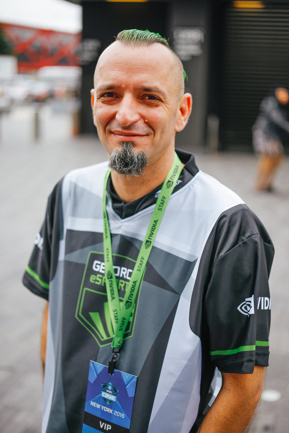 A man with green hair and matching Nvidia accessories stands outside of the Barclay Center during ESL One NY.