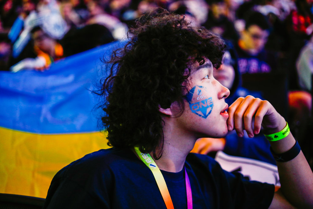 A fan holds up a Ukrainian flag silhouetting a man with an ESL One tattoo who watches the tournament in rapt attention.