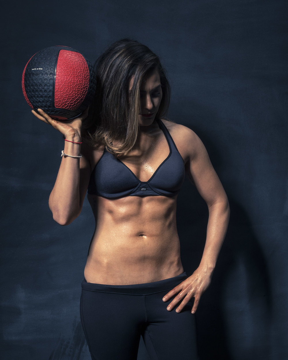 Toronto fitness model and personal trainer Bianca posing in studio showing off her abs.