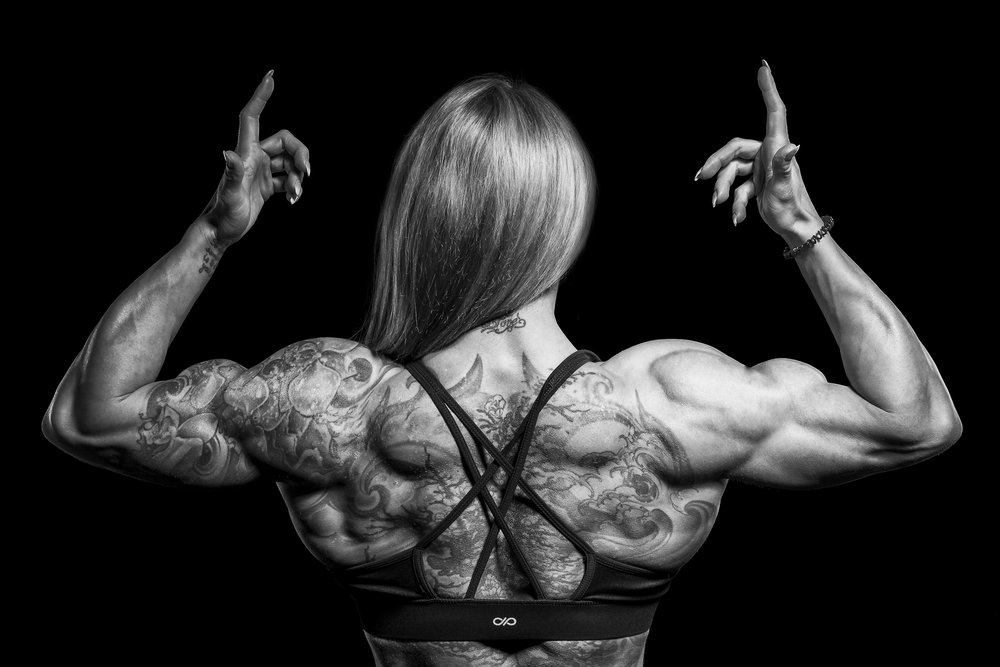 Female bodybuilder flexes her back.