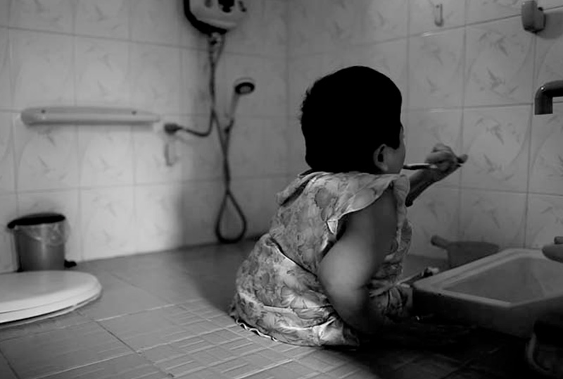 Thao brushing her teeth in a bathroom her father made to suit her specific needs.