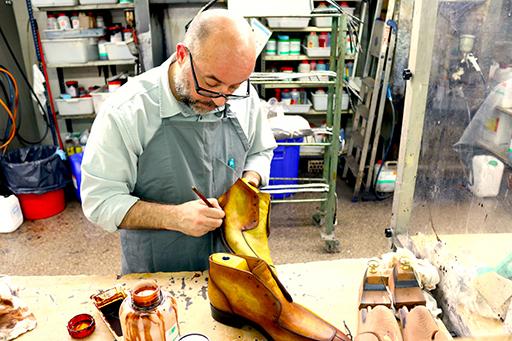 Cobbler Union's master shoemaker, Miquel, applies a patina on a pair of Renoir boots.