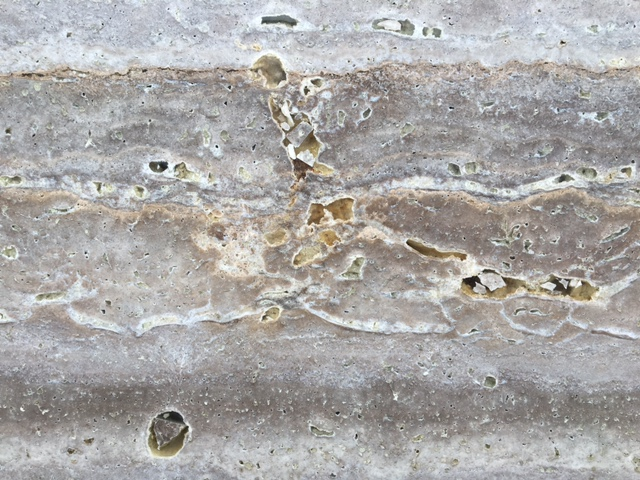 Pits filled with resin in a slab of Noce Travertine