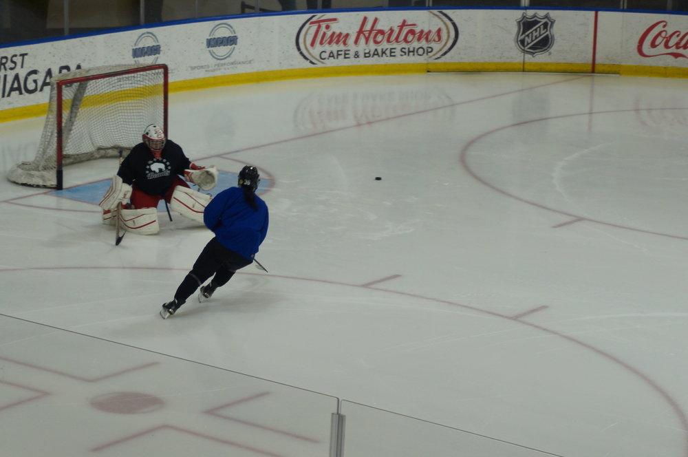 Neumann tracks the puck after a save on Kourtney Kunichika
