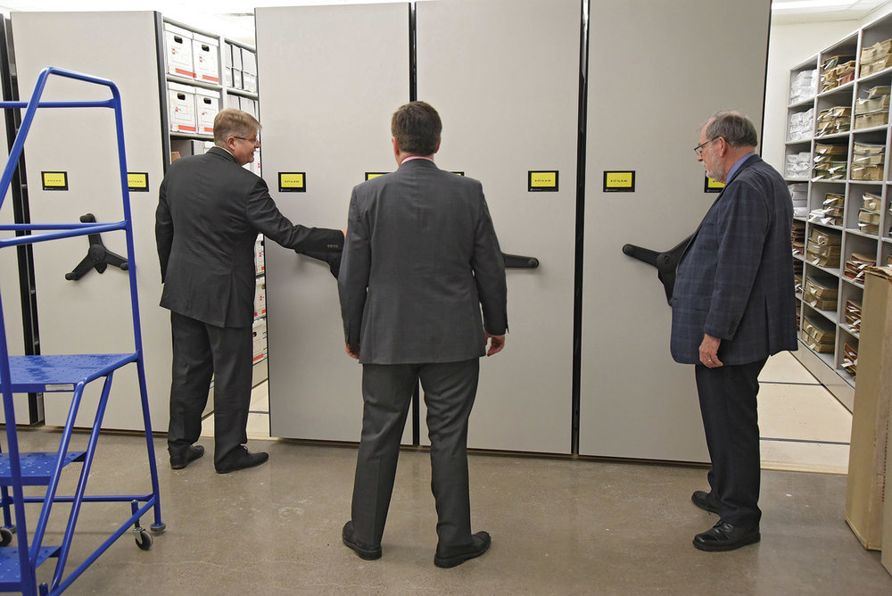 The new archives, on the second floor of the library building at 254 Pinnacle Street, provides 5,000 square feet of storage and work space meeting modern archival standards. Mark Fluhrer, Neil Ellis and Orland French sample the state-of-the-art rolling doors that provide access to materials.Photo by Bob House / courtesy Community Archives of Belleville and Hastings County