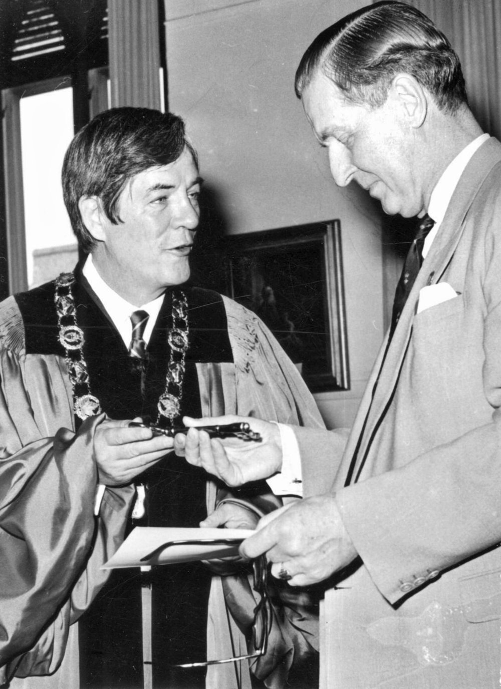 Russell Scott, wearing chain of office as mayor of Belleville, is shown presenting the key to the city to an unidentified recipient. Dr. Scott was distinguished by an approachable and down-to-earth demeanour. Photo courtesy of Belleville and Hastings County Community Archives.