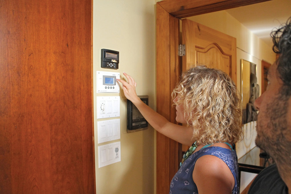 Michele's wife Madonna shows off the thermostat-like panel that indicates energy storage and usage.