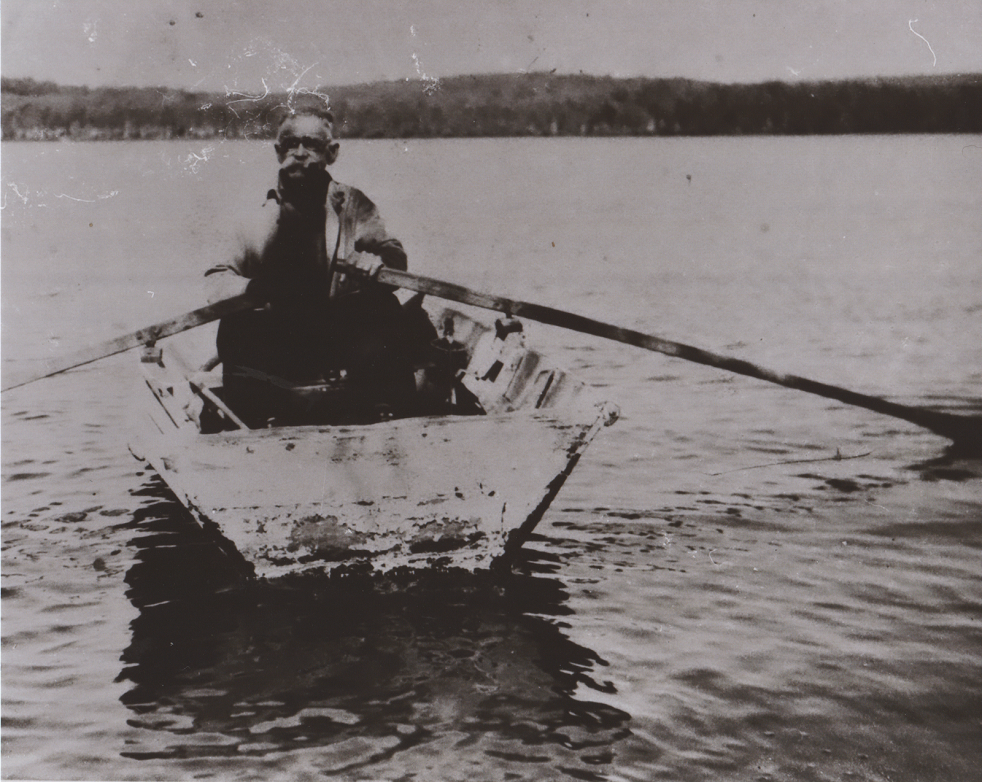 """Ole Joe"" rowing on Lake St. Peter Lake in a wooden boat he himself built."