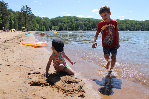 The public beach at Papineau Lake is popular with young families because of its sandy beach and shallow water.