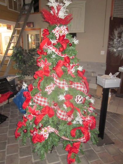 "Tying a variety of red ribbons around this Christmas tree makes for an inviting ""Country Santa"" feeling."
