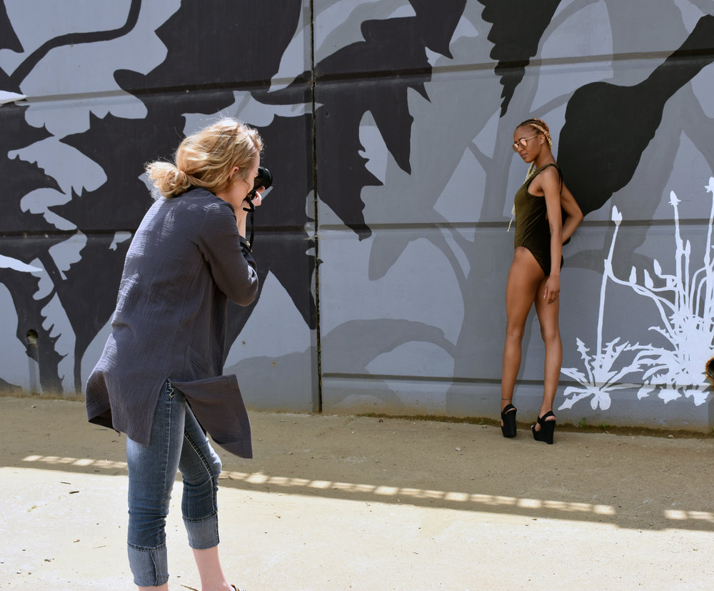 Our photographer Amber getting a shot of our model in this adorable black and gold one piece!