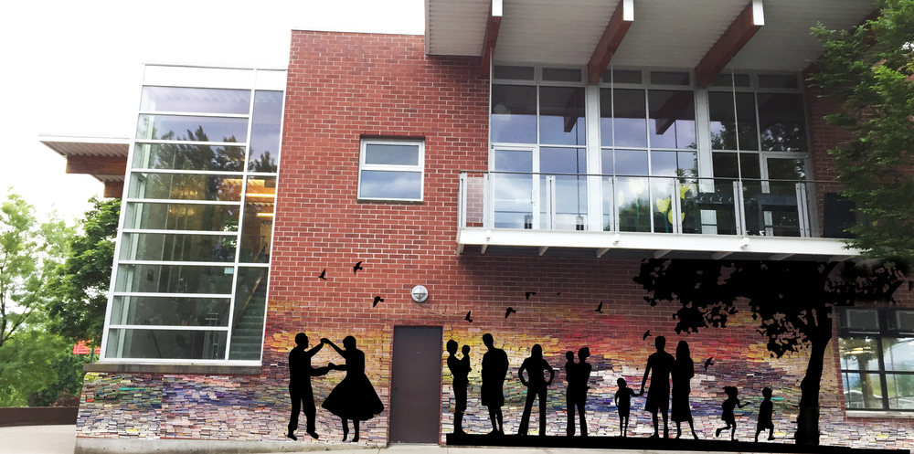 Silhouettes display a range of community dancing and enjoying a picnic. in the background the bricks transform into a mosaic of many coloured books. The book represent knowledge and our diverse stories. Alone each book is different and unique. Together the books form a strong wall which represent the power of connected community. The crows also signify community and Thunderbird's location on the crow path.