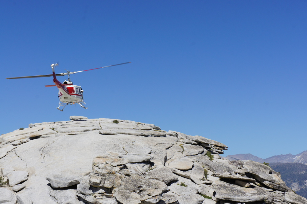 A hiker being air lifted from the top of Half Dome