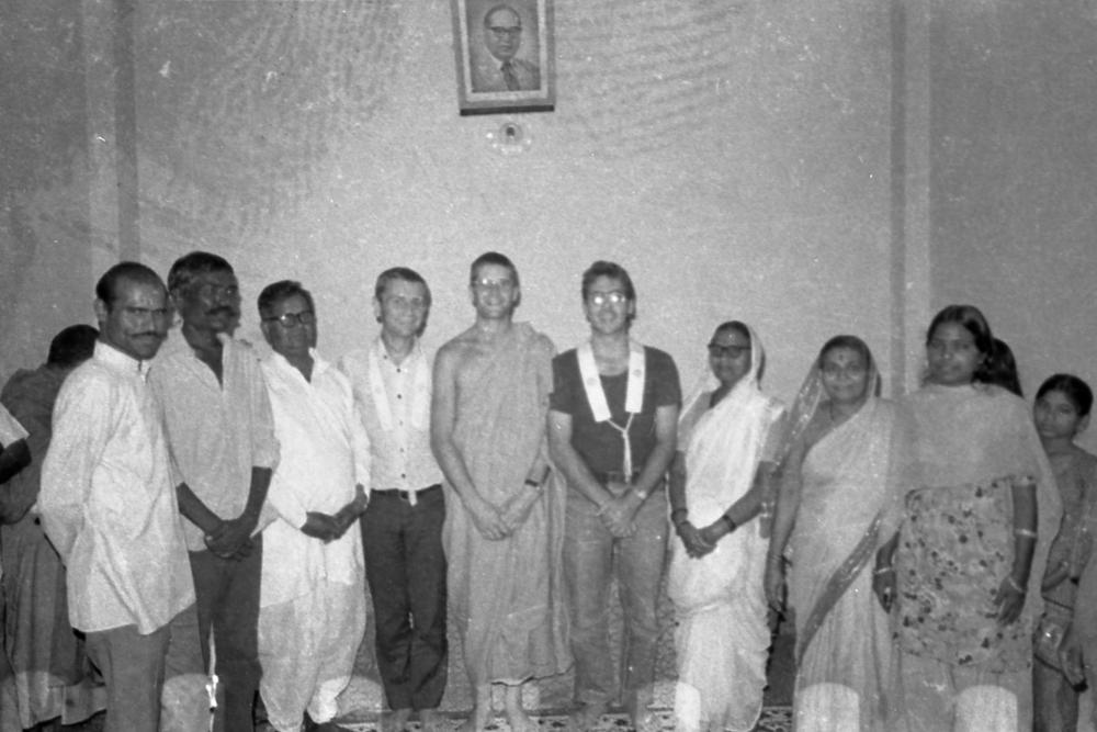 This is a picture taken in Ambedkar societyin Pune, where we had our office. Your mother is there…can you recognize her? She must have been around 20 then.       At that ceremony she became what we call a Mitra. She wanted to formally associate with us and involve herself in deeper spiritual practice. She was very determined. Her family was very poor, her father working but not getting very much for it.       The very large man in the picture is Shakyanand, who worked with us. A real character. He would eat 7 meals a day, and everyday for lunch he'd bring a big dabba, a tiffin box that he'd always share around with us. When he retired properly he became a monk and travelled all the time, not staying in any place for more than 3 days. He was old, had diabetes, had absolutely everything wrong with him, but he'd just keep going .     The one next to your mother is Mrs. Wanshil, who sold vegetables outside her house everyday. Her husband would sometimes bring up to thirty people to our meditation classes! All his children, grandchildren, nephews and nieces! Just gives you a sort of idea of the people we were working with.