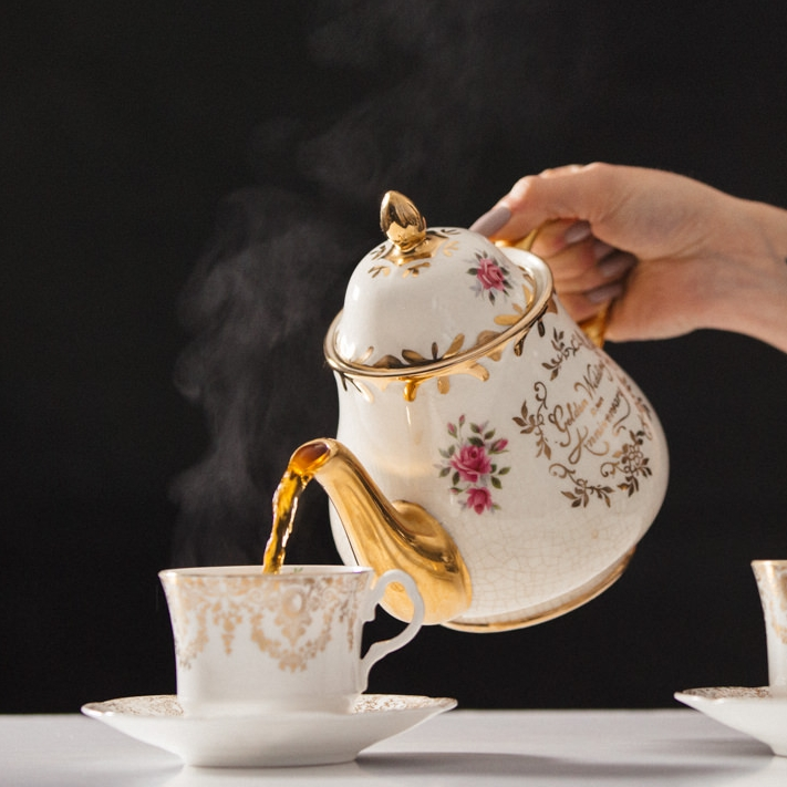 Pouring freshly brewed speciality tea from a vintage china teapot with inscription Golden Wedding Anniversary into a gold and white china teacup and saucer.