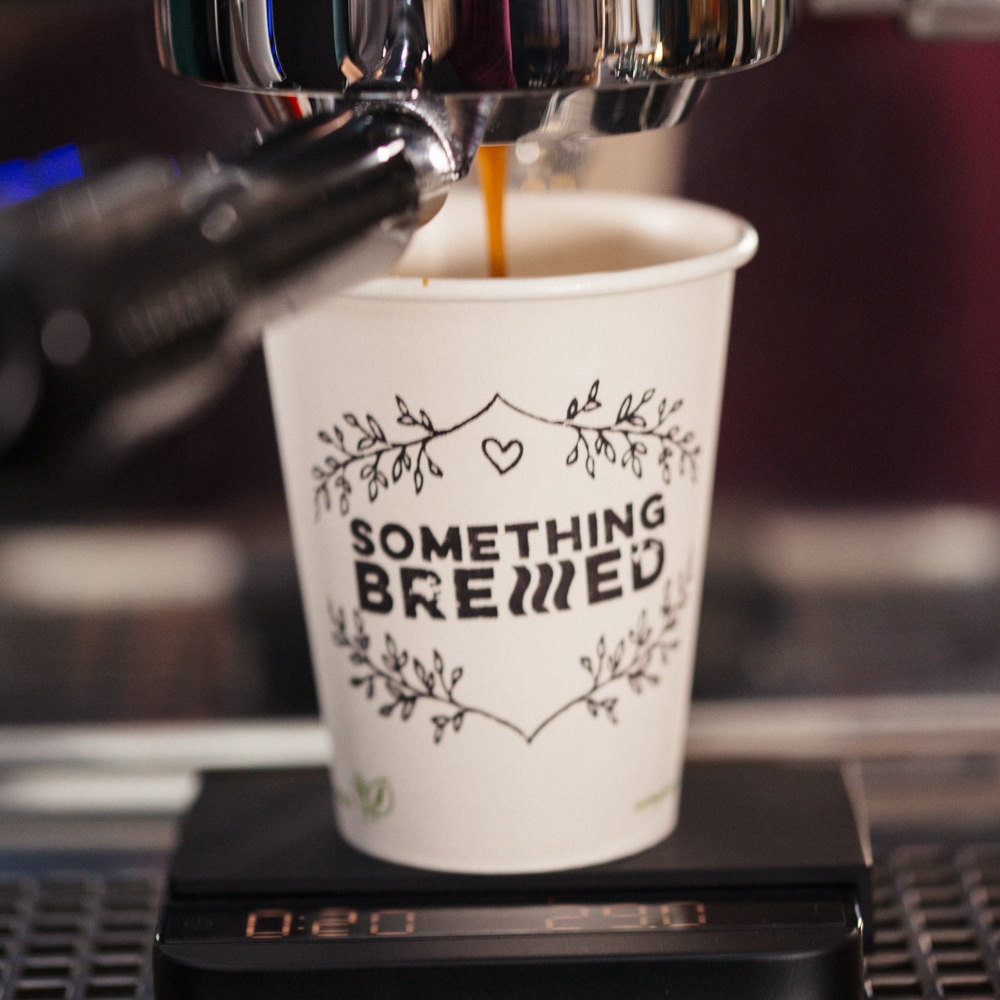Speciality Coffee Espresso being poured into a fully compostable paper cup from a naked portafilter being weighed and timed from Something Brewed.