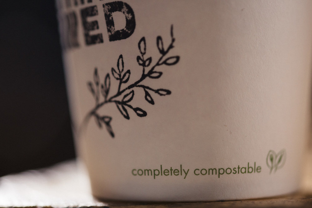 """completely compostable"" declaration on the side of a White Vegware paper cup with ""Something Brewed"" stamp."