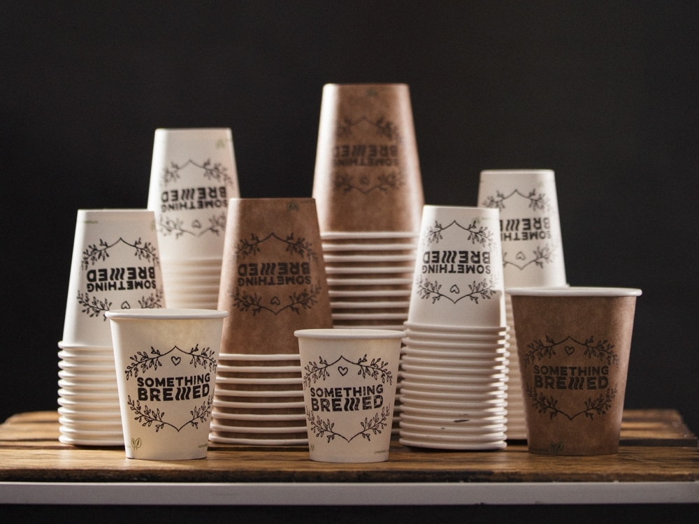 "A selection of Vegware Cups in 3 different sizes and 2 colours with ""Something Brewed"" stamp"