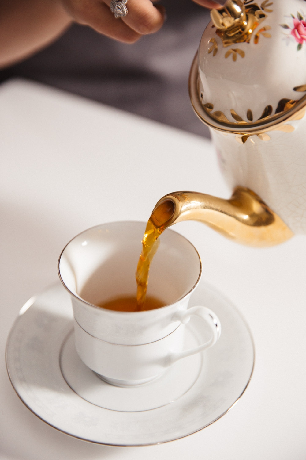 Pouring speciality tea from a vintage white teapot into a white and silver teacup.