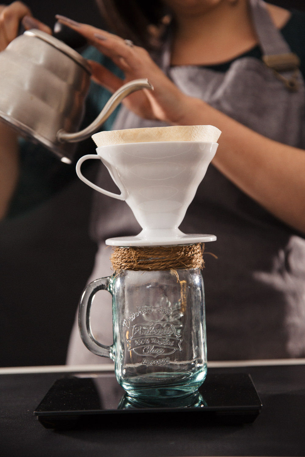 Something Brewed Mobile Coffee Bar & Afternoon Tea Caterers for hire: Weddings, Corporate & Events using Speciality Coffee.  Glasgow, Edinburgh & Scotland pouring V60 filter coffee into a vintage mason jar with twine