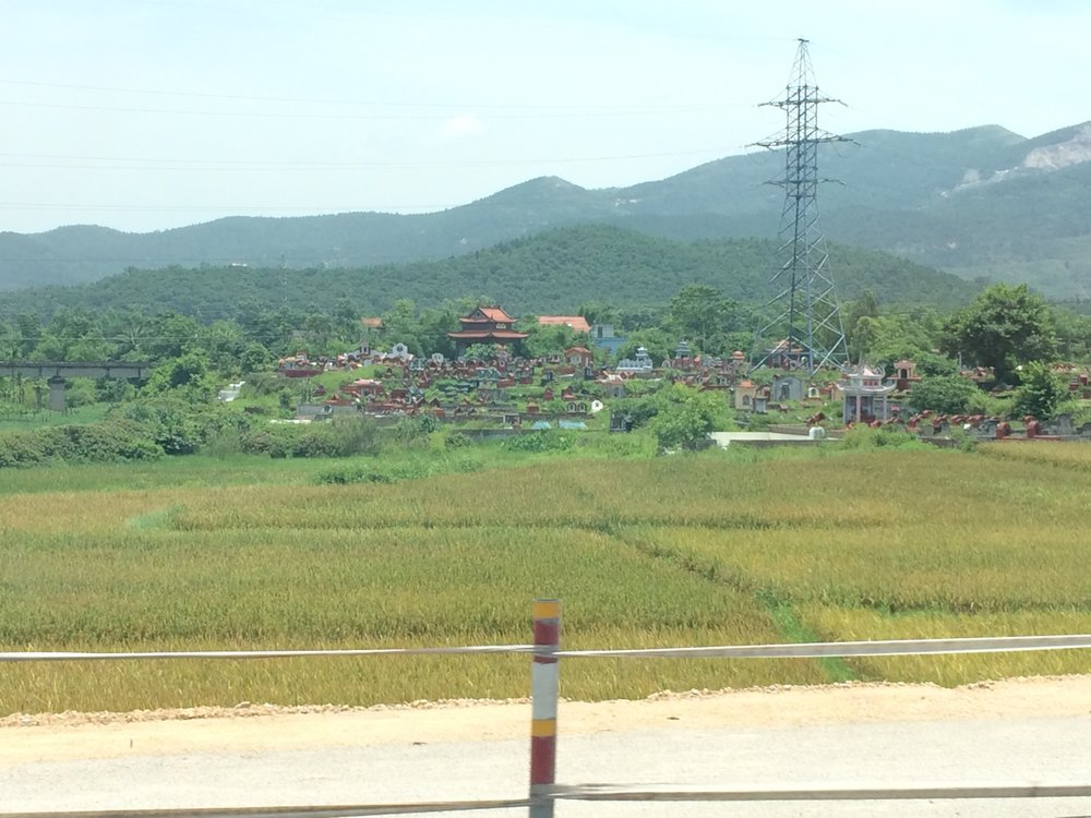 Why are graveyards in the Vietnamese countryside on slight hilltops?