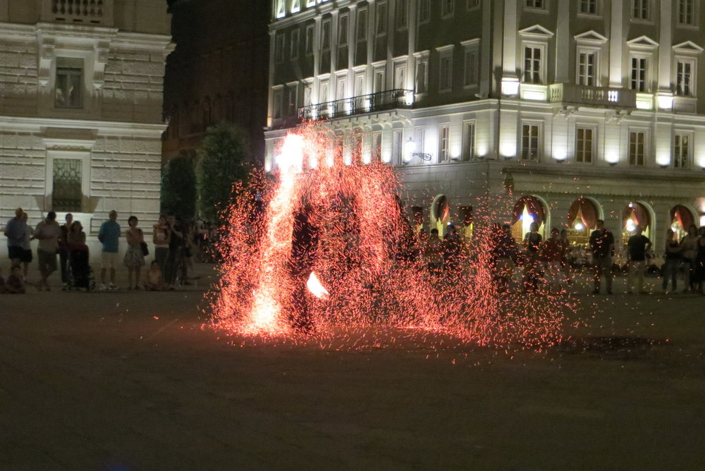 Fire spinner in Piazza dell'Unità in Trieste, Italy