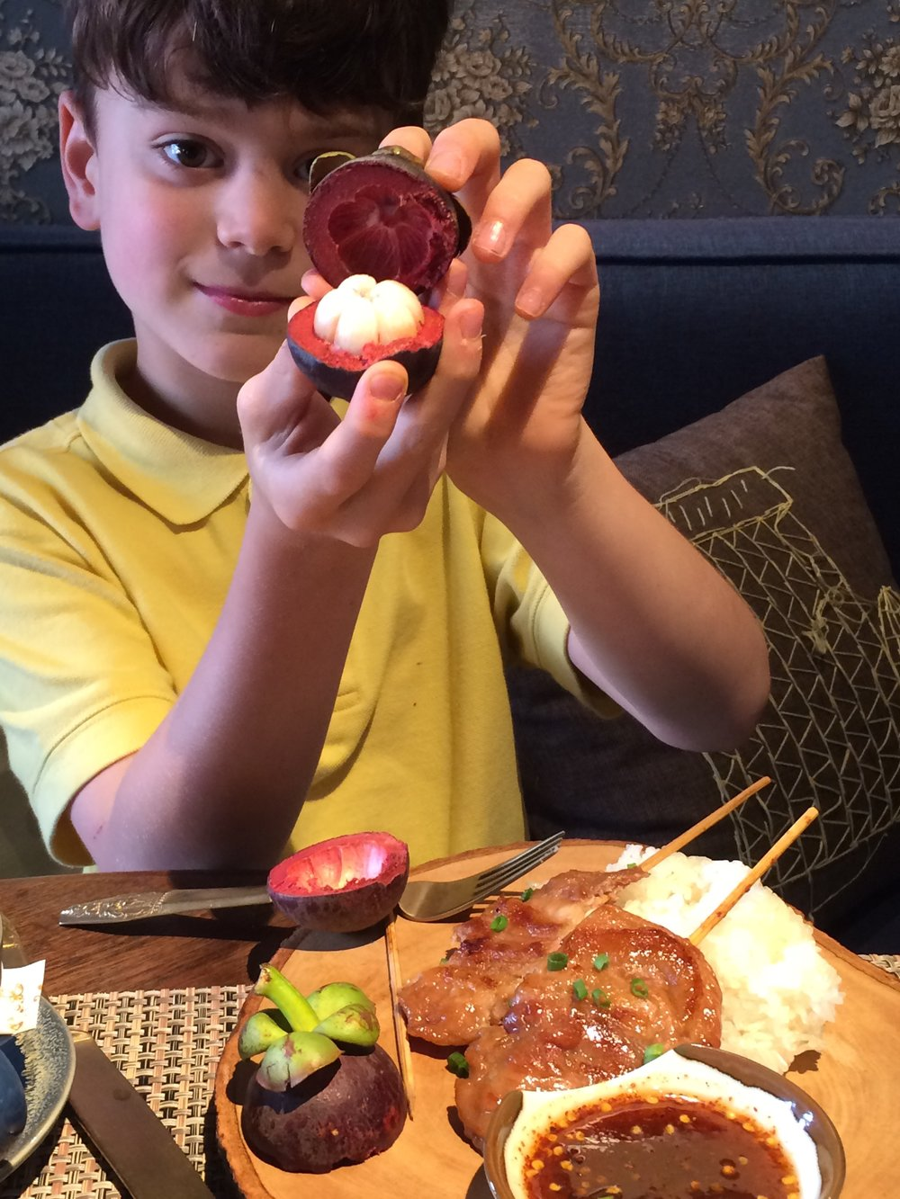 Gabe's first mangosteen at our first breakfast in Bangkok