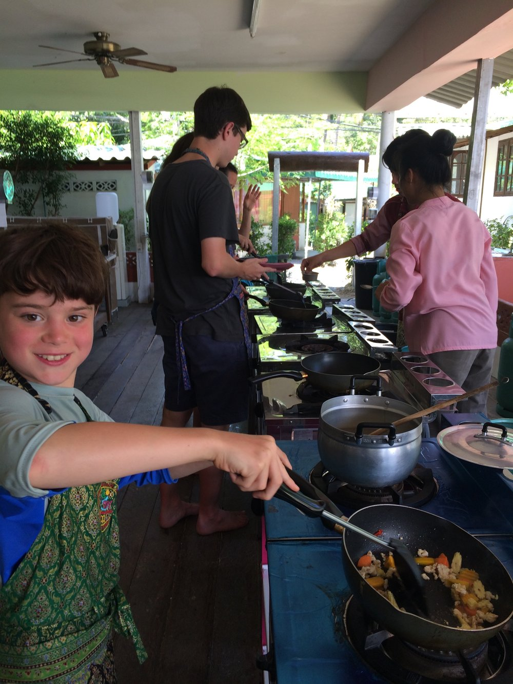 Gabe cooking in Thailand. In his swimsuit. As one does.