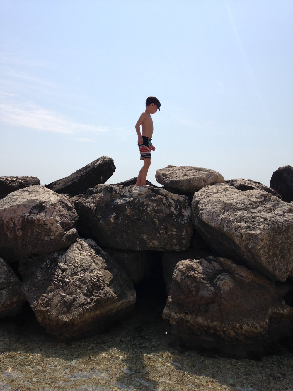 Gabe on the rocks of the beach in Le Marche, Italy
