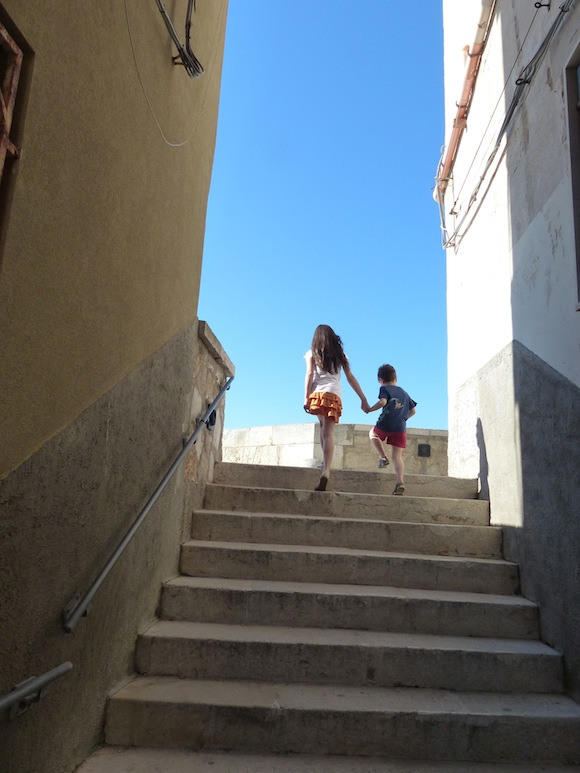 Kids climb the steps in Trapani, Sicily, Italy