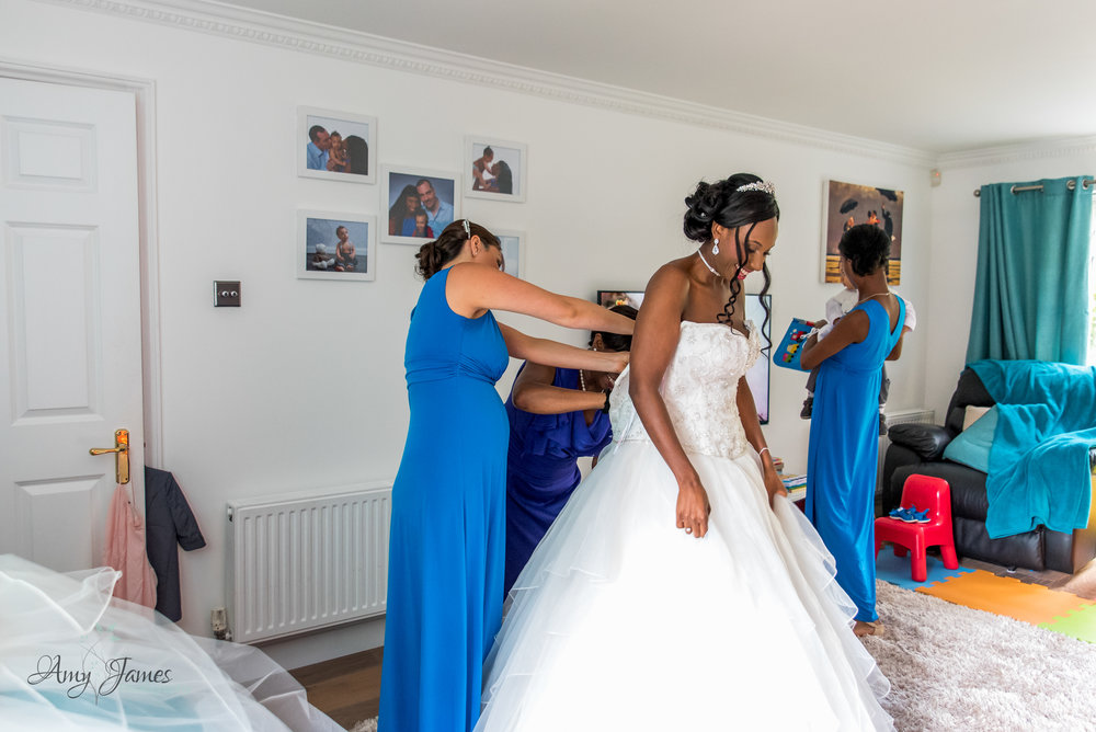 Bride getting into dress for Four Seasons Hotel Hampshire wedding by Amy James Photography - documentary wedding photographer for Hampshire and Surrey