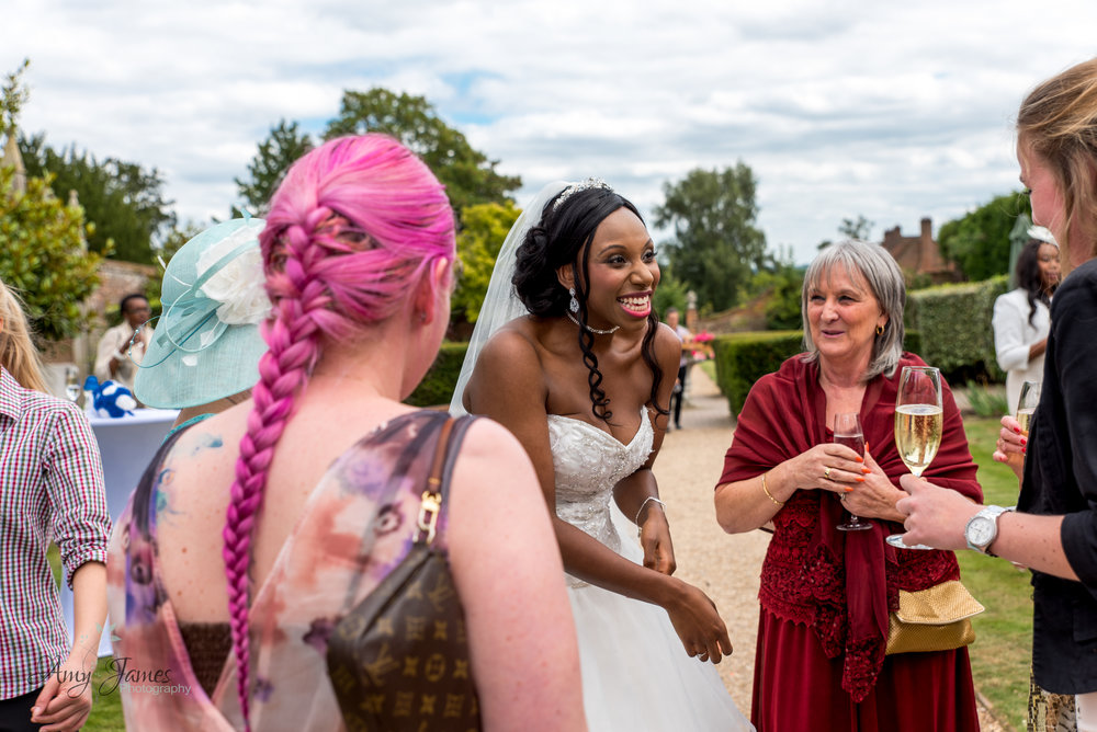 bride laughing at outside drinks reception by Amy James photography at four seasons hotel Hampshire