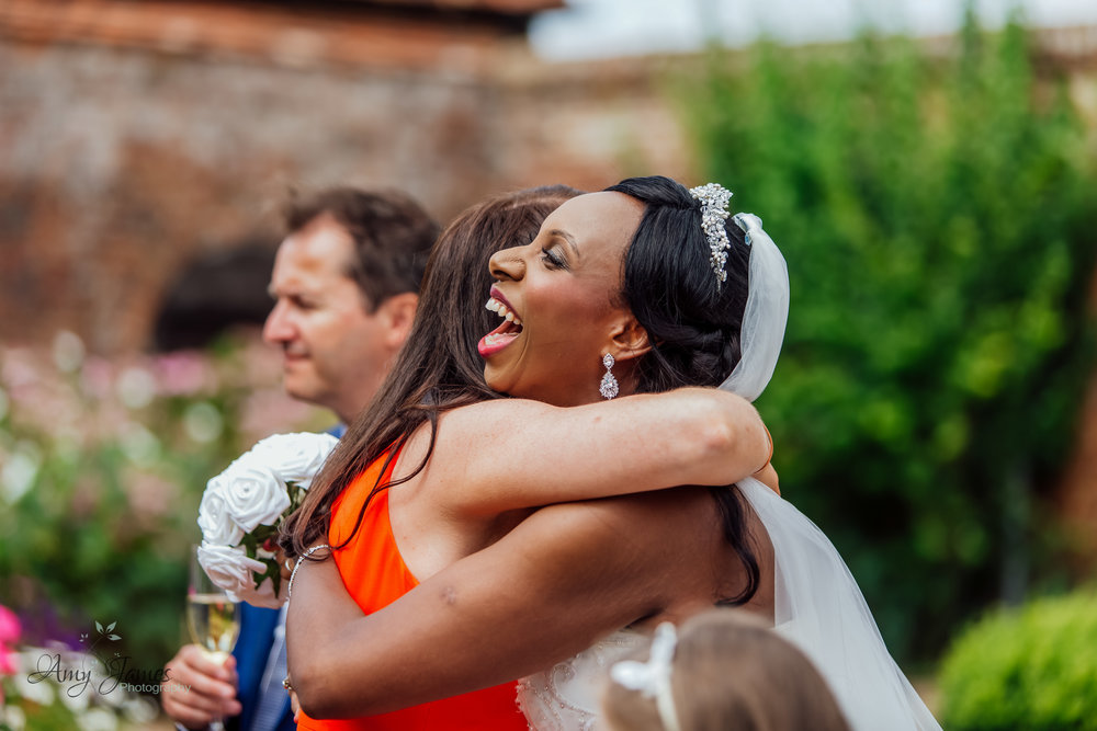 Bride hugging friend at Four Season Hotel Wedding Hampshire by Amy James Photography - documentary wedding photographer