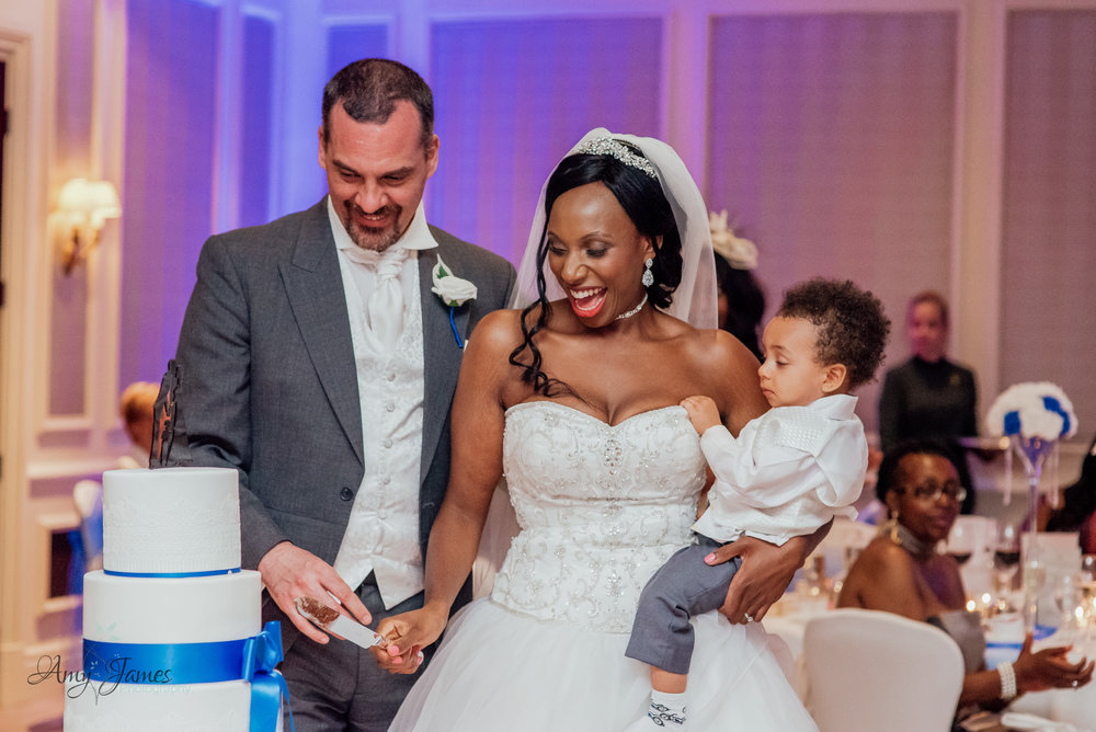 Bride and groom cutting the wedding cake at The Four Seasons Hotel Hampshire by Amy James photography Hampshire wedding photographer