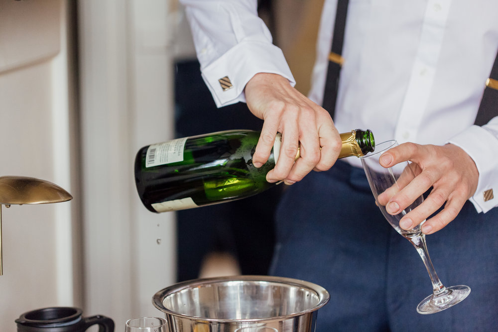 Groom pouring champagne at The Elvetham Wedding Venue by Amy James photography Wedding Photographer Hampshire