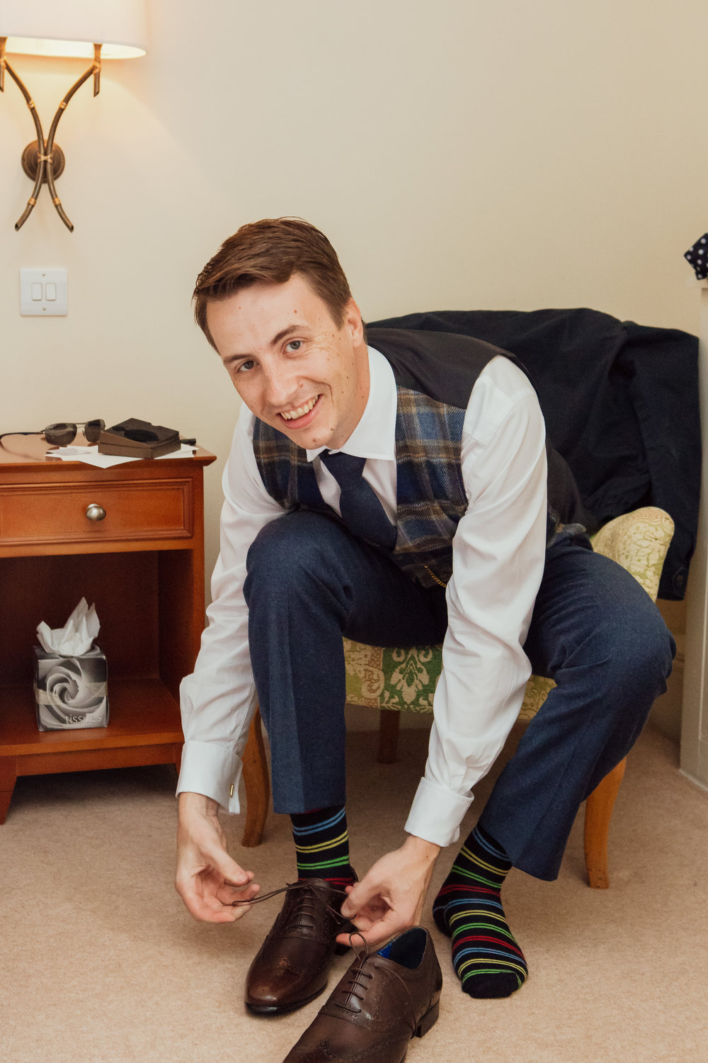 Groom tying his shoes before his wedding at The Elvetham Wedding Venue Hampshire by Amy James Photography - Wedding photographer Hampshire