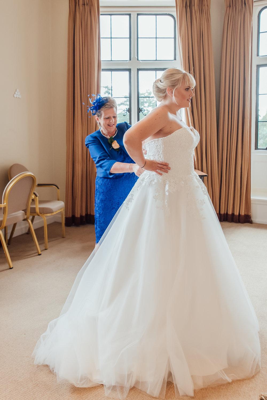 Brides Mum doing up her wedding dress photo by Amy James Photography Hampshire Wedding Photographer