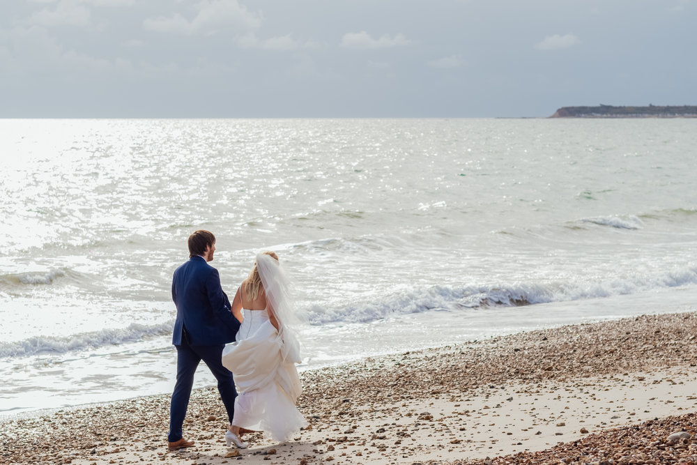 Highcliffe Castle Wedding - beach wedding - Bride and Groom walking along breach - Amy James Photography - Wedding Photographer Hampshire
