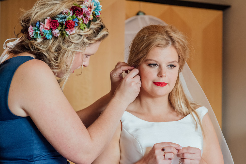 Bridesmaid helping bride get ready for her wedding at The Kings Arms Hotel Christchurch - Amy James Photography - Documentary wedding photographer for Hampshire Dorset and Surrey